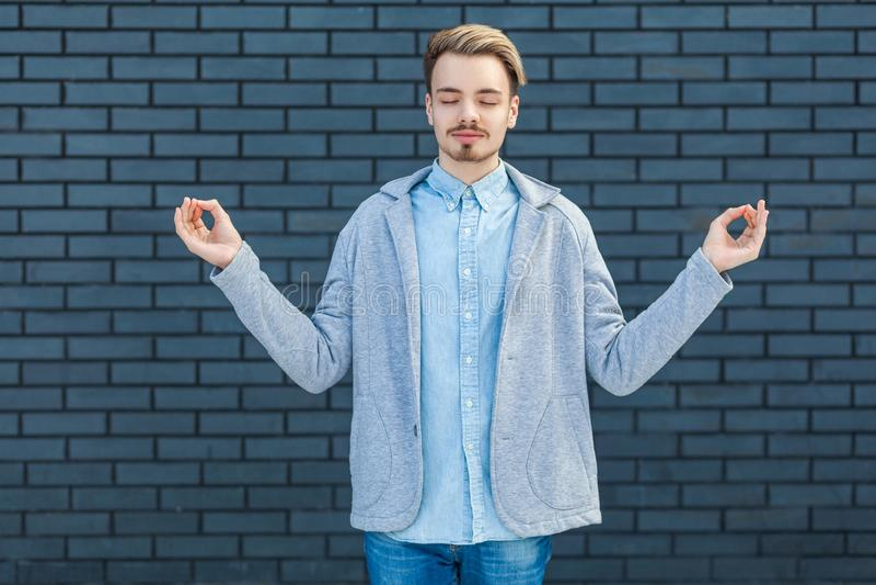 Ståenden av den lugna allvarliga stiliga unga blonda mannen i tillfällig stil som står i yoga, poserar, stängda ögon och kopplat  royaltyfri foto