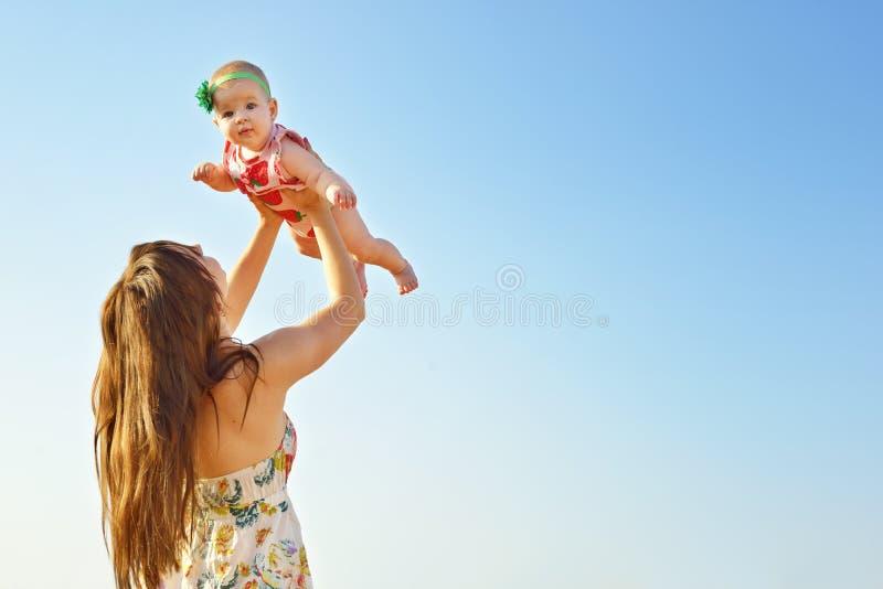 Ståenden av den lyckliga älska modern och hon behandla som ett barn utomhus Moder och barn mot blå himmel för sommar royaltyfri bild