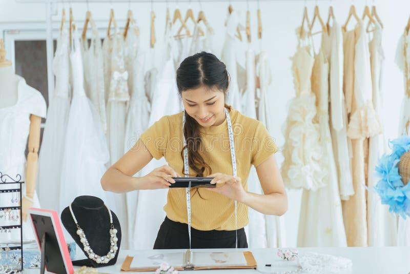 Ståenden av den lyckliga asiatiska ägaren för kvinnabröllopsklänninglagret arbetar, shoppar den härliga sömmerskan i och små och  royaltyfri fotografi
