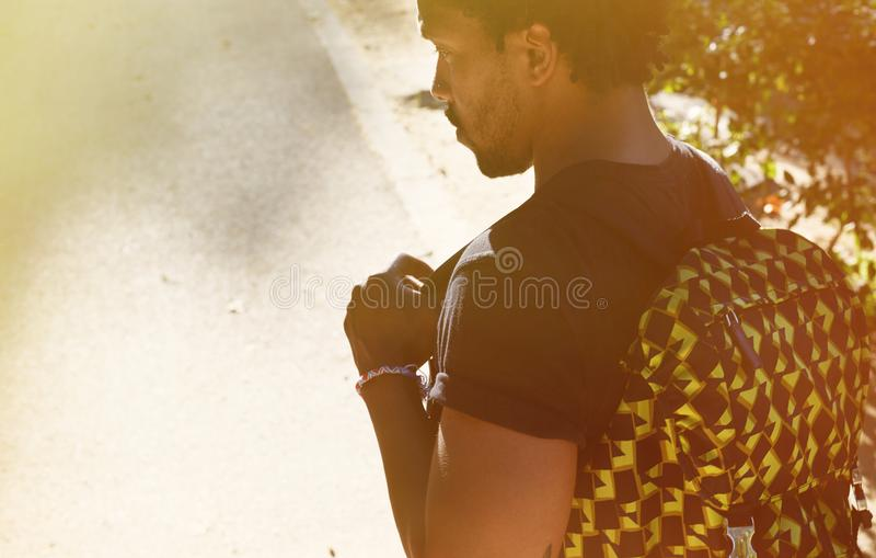 Ståenden av den lyckliga attraktiva unga afrikansk amerikanhipsteren i tillfälliga kläder som går på staden, parkerar med ryggsäc fotografering för bildbyråer