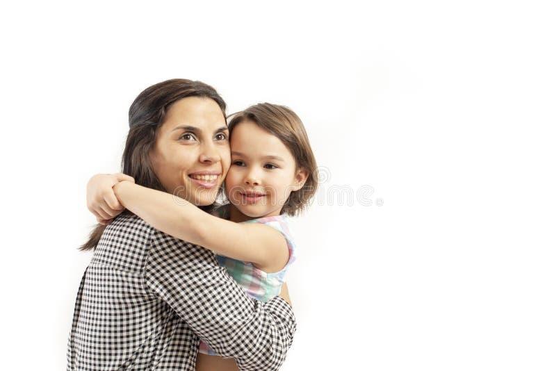 Ståenden av den lyckliga dottern omfamnar hennes moder som isoleras på vit bakgrund fotografering för bildbyråer