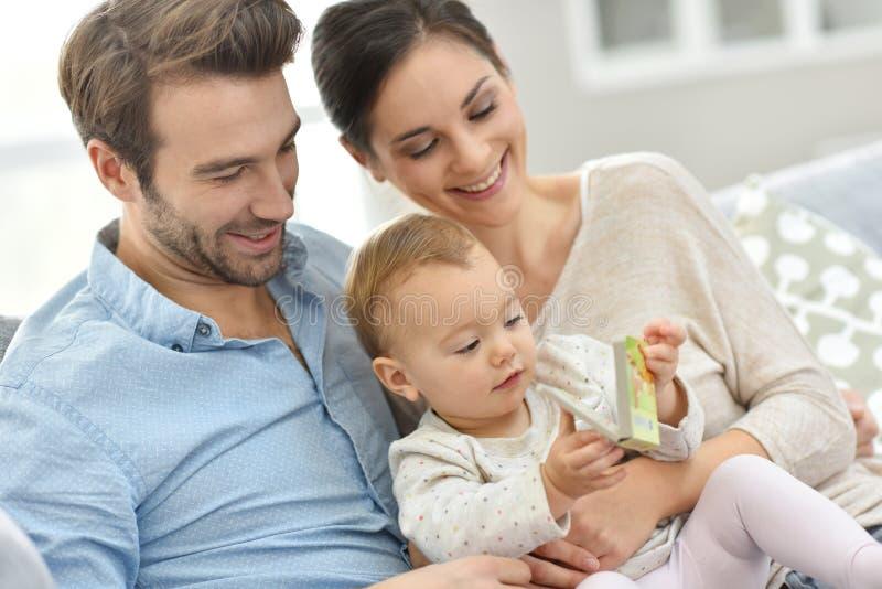 Ståenden av den lyckliga familjen med behandla som ett barn den läs- barnboken arkivbilder