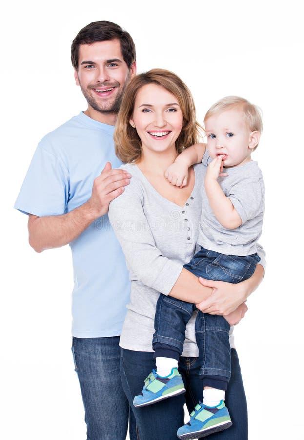 Ståenden av den lyckliga familjen med lite behandla som ett barn. arkivfoton