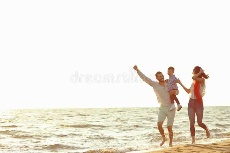 Ståenden av den lyckliga familjen och behandla som ett barn tycka om solnedgång i sommarfritiden royaltyfria foton