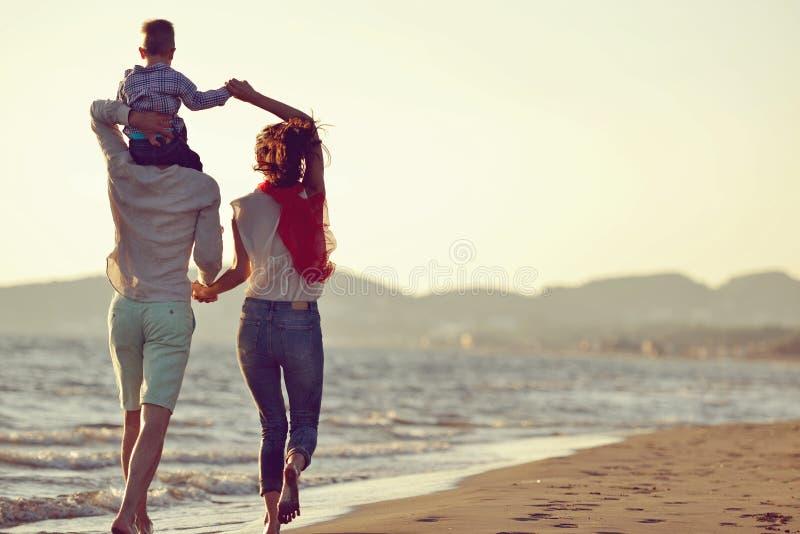 Ståenden av den lyckliga familjen och behandla som ett barn tycka om solnedgång i sommarfritiden arkivbilder