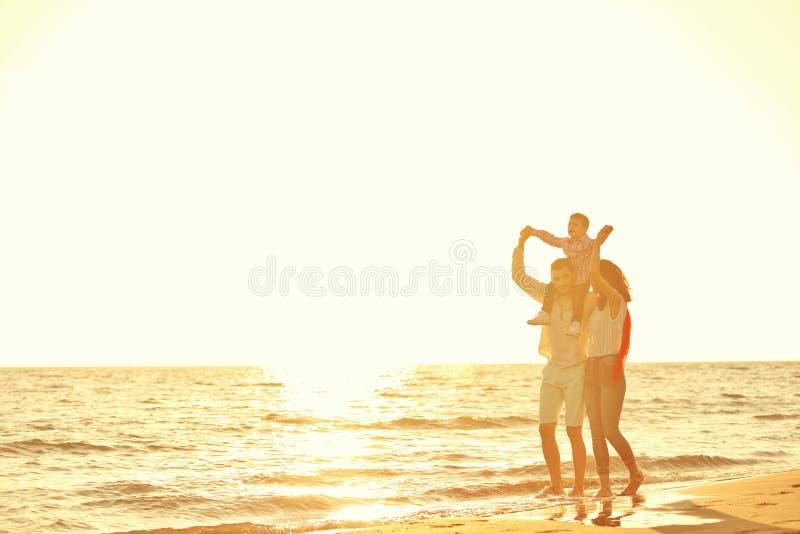 Ståenden av den lyckliga familjen och behandla som ett barn tycka om solnedgång i sommarfritiden arkivbild