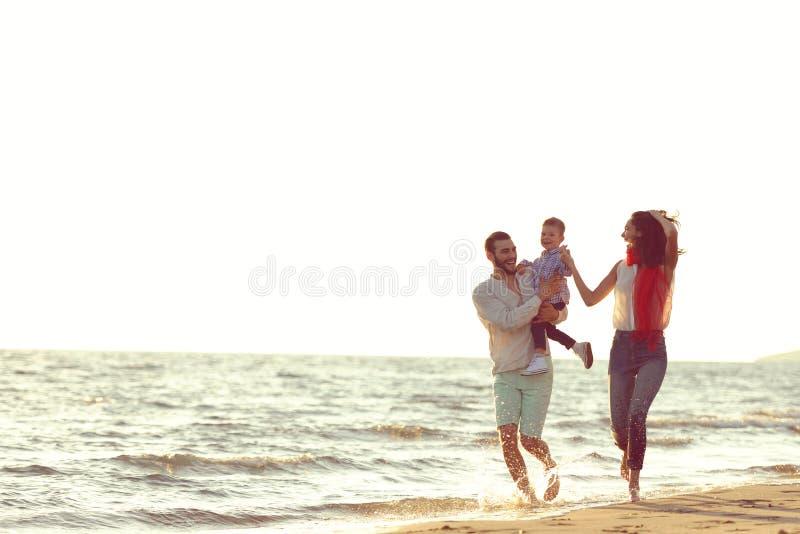 Ståenden av den lyckliga familjen och behandla som ett barn tycka om solnedgång i sommarfritiden arkivfoto
