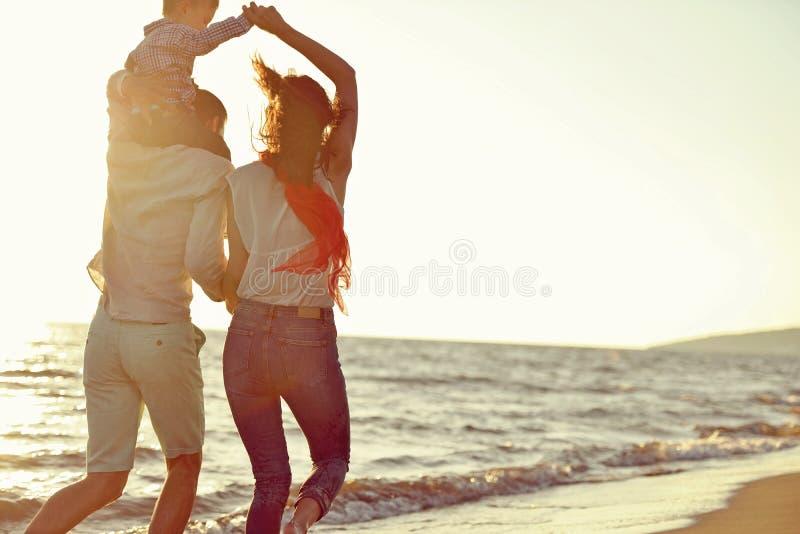 Ståenden av den lyckliga familjen och behandla som ett barn tycka om solnedgång i sommarfritiden arkivfoton