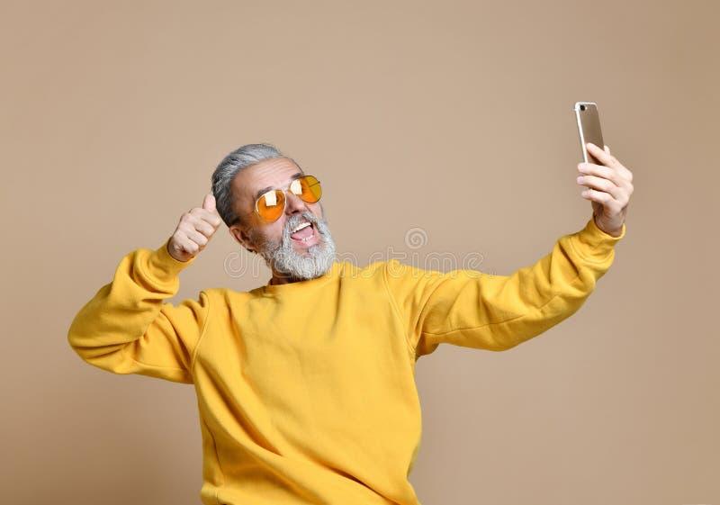Ståenden av den lyckliga höga miljonärmannen som använder smartphonemobiltelefonen, gör selfie i gul solglasögon fotografering för bildbyråer