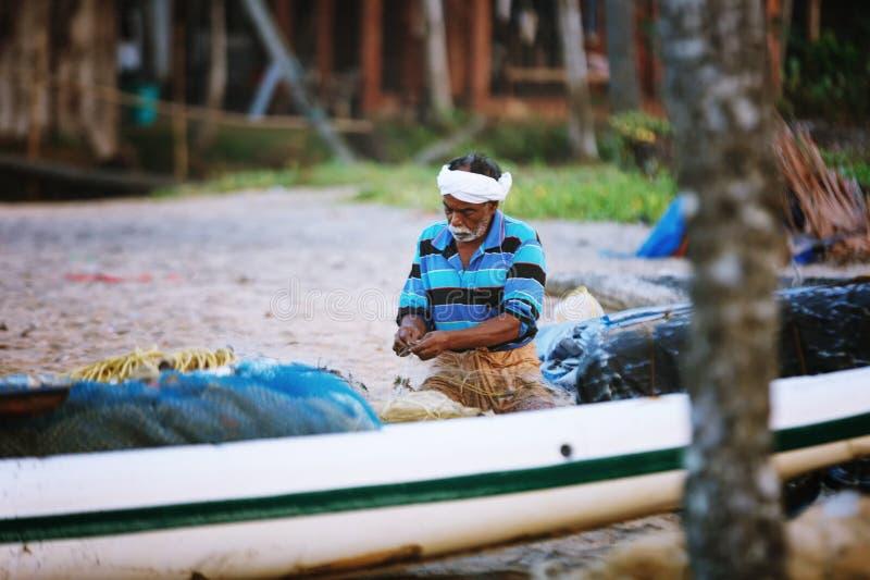 Ståenden av den lyckliga indiska fiskaren river upp fisknät och redskapet, medan sitta i ett fartyg, Kerala Indien fiskerigolf Od royaltyfri foto