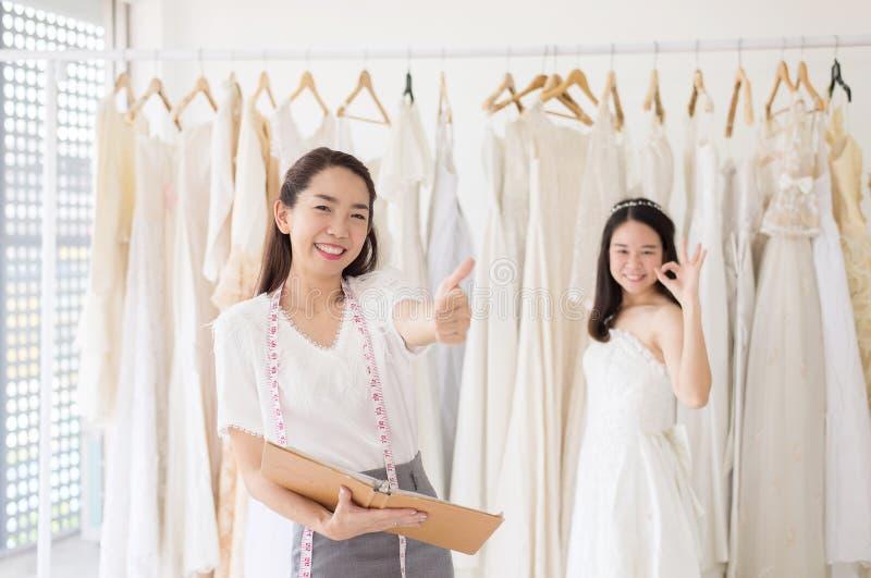 Ståenden av den lyckliga kvinnainnehavkreditkorten i bröllopsklänninglagerägare, den härliga lyckade sömmerskan shoppar in och sm royaltyfri foto