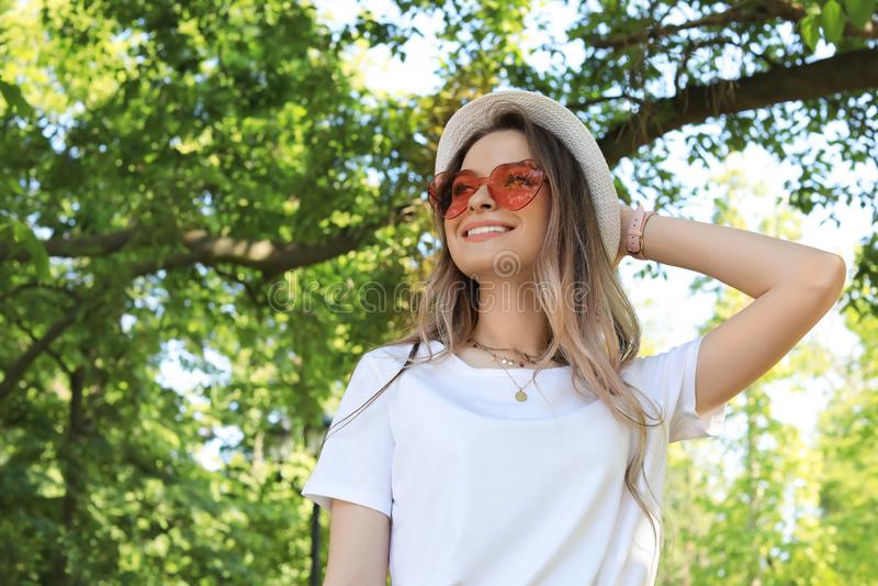 Ståenden av den lyckliga kvinnan med hjärta formade exponeringsglas i sommar parkerar fotografering för bildbyråer