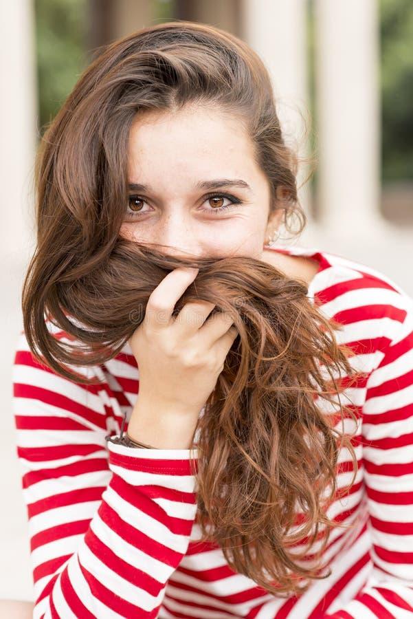 Ståenden av den lyckliga kvinnan täcker hennes framsida med hår, frisyr lurar fotografering för bildbyråer