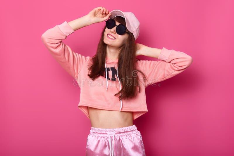 Ståenden av den lyckliga le Caucasian brunettflickan i den stilfulla korta hoodien, sweatpants och rosa lock, bär svart solglasög arkivbilder