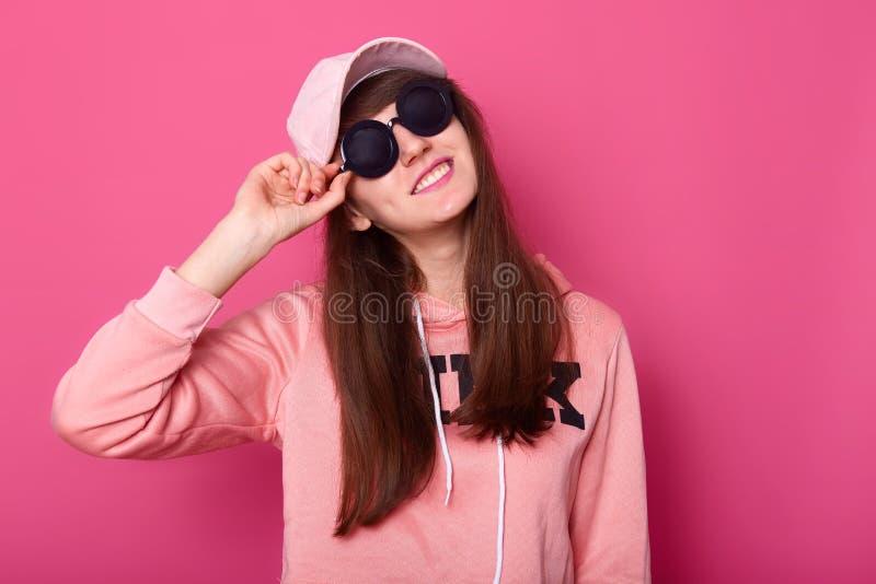 St?enden av den lyckliga le Caucasian brunettton?ringen i stilfull kort rosa hoodie, steg locket, svart solglas?gon, rymmer hads  royaltyfri bild