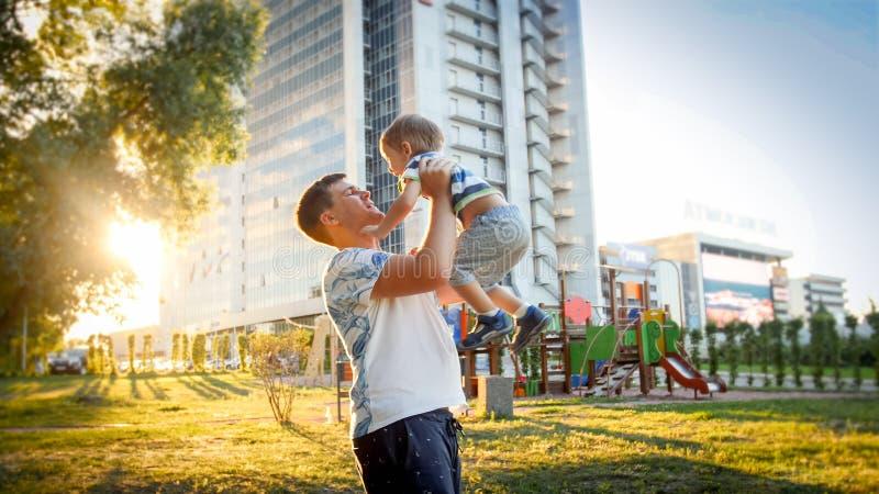 Ståenden av den lyckliga le unga fadern som upp rymmer och kastar hans skratta gamla lilla son för 3 yearas parkerar in, på arkivfoton