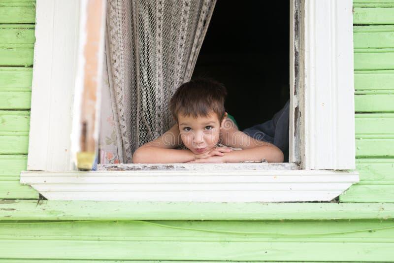 Ståenden av den lyckliga lilla le pojkeungen ser ut ur lantligt träfönster och att le unga vuxen människa Gammalt lantligt fotografering för bildbyråer