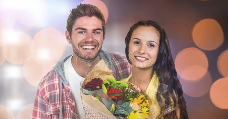 Ståenden av den lyckliga mannen av kvinnainnehavet blommar över bokeh royaltyfria foton