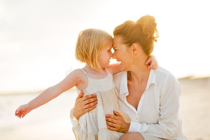Ståenden av den lyckliga modern och behandla som ett barn att krama för flicka arkivbild