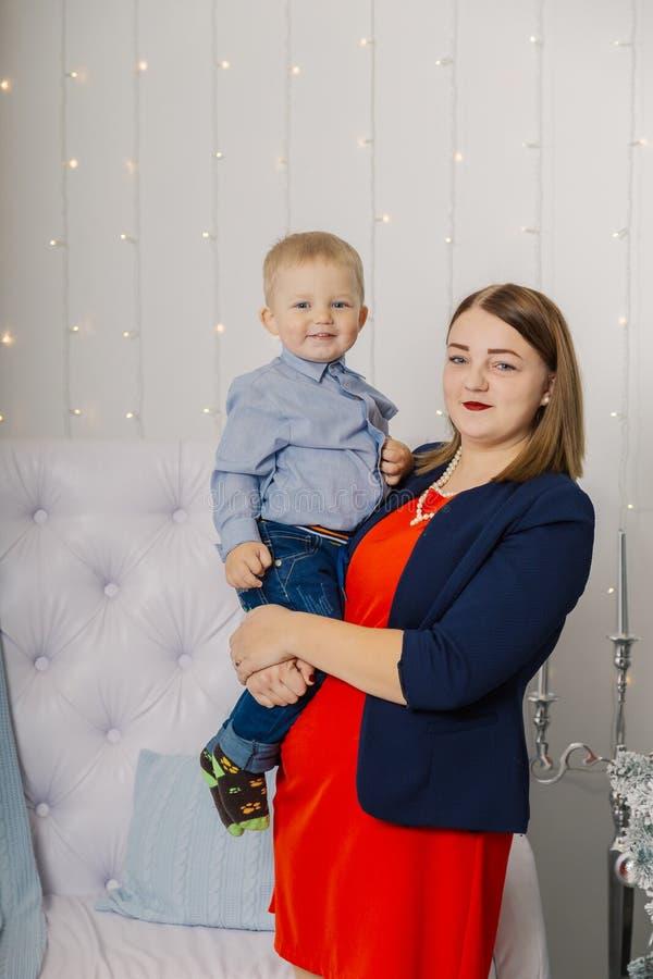 Ståenden av den lyckliga modern och förtjusande behandla som ett barn firar jul Ferier för ` s för nytt år Litet barn med mamman  royaltyfri foto