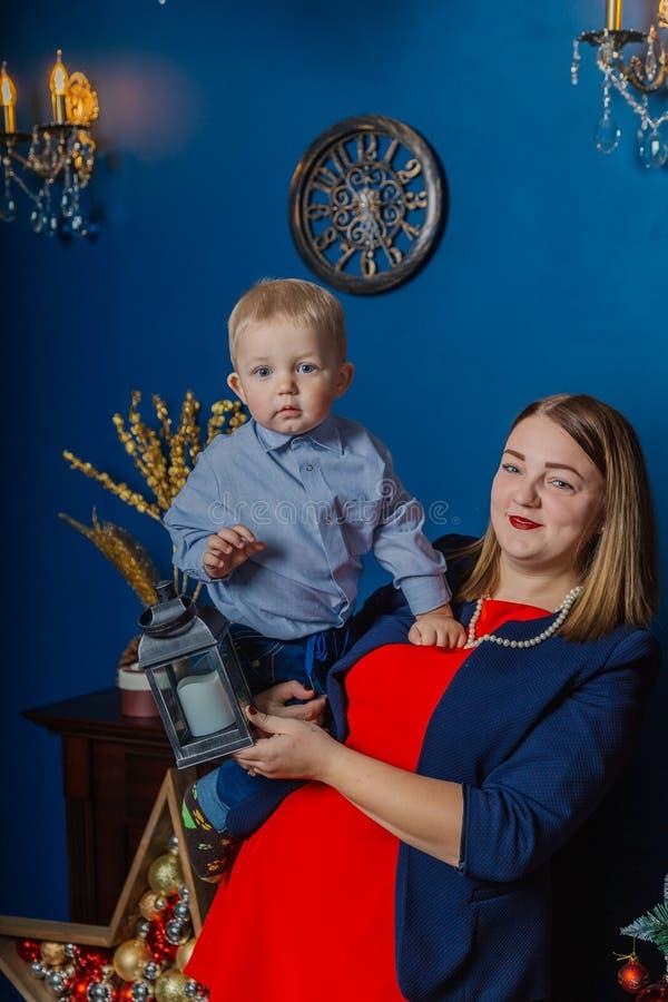 Ståenden av den lyckliga modern och förtjusande behandla som ett barn firar jul Ferier för ` s för nytt år Litet barn med mamman  arkivbild