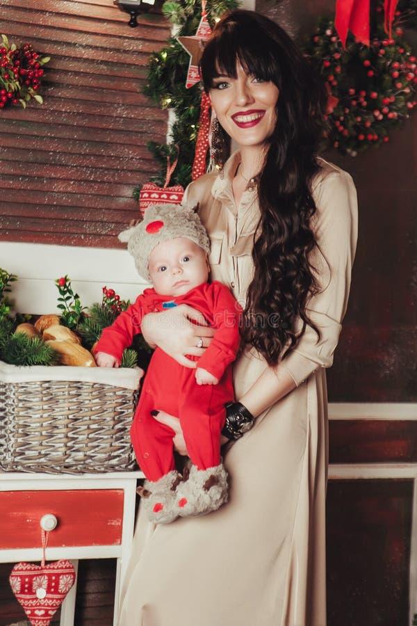 Ståenden av den lyckliga modern och förtjusande behandla som ett barn i dräkt av den lilla hjälpredan för jultomten` s royaltyfri bild