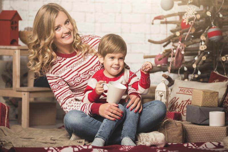 Ståenden av den lyckliga modern och sonen på bakgrunden av julgranen i nytt år hyr rum Idén för vykort royaltyfria bilder