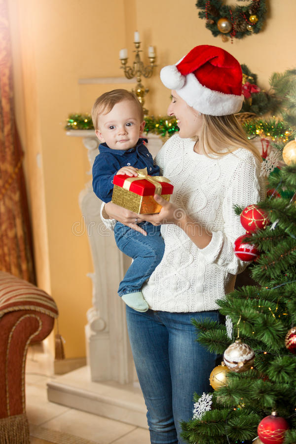 Ståenden av den lyckliga modern som ger gåva till henne, behandla som ett barn sonen på Chris royaltyfri bild