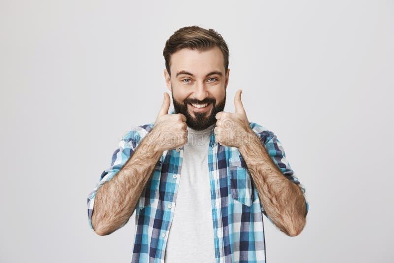 Ståenden av den lyckliga skäggiga mannen med skinande leendevisninggoda eller gör perfekt gest med tummar upp, över grå bakgrund arkivbild