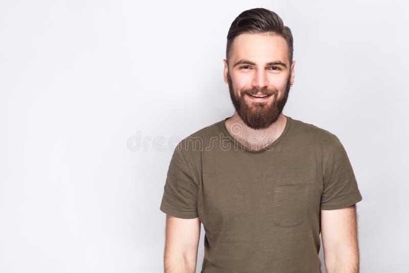 Ståenden av den lyckliga smileyen uppsökte mannen med mörker - grön t-skjorta mot ljus - grå bakgrund royaltyfri foto