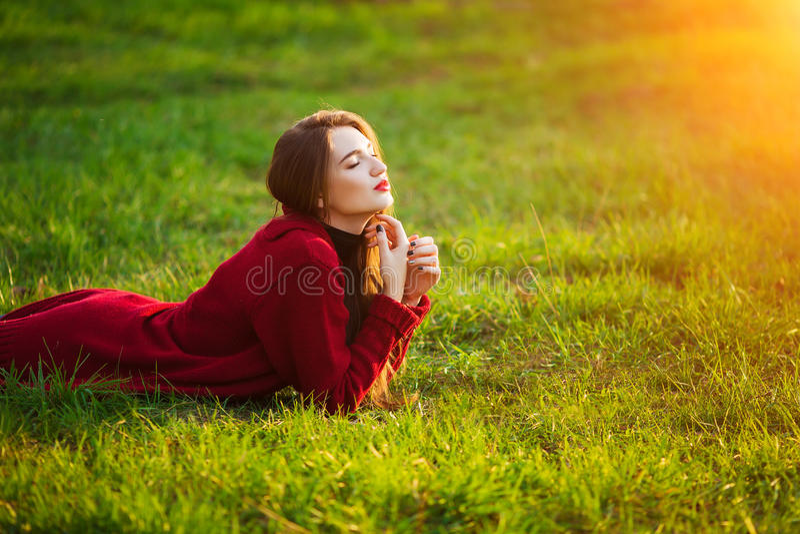 Ståenden av den lyckliga sportiga kvinnan som in kopplar av, parkerar på grön äng Glad kvinnlig modell som utomhus andas ny luft royaltyfri foto
