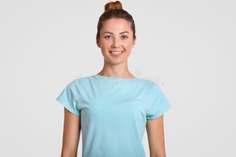 Ståenden av den lyckliga tonårs- flickan med det toothy leendet, förtjust uttryck, bär den tillfälliga t-skjortan och att vara i  royaltyfri foto