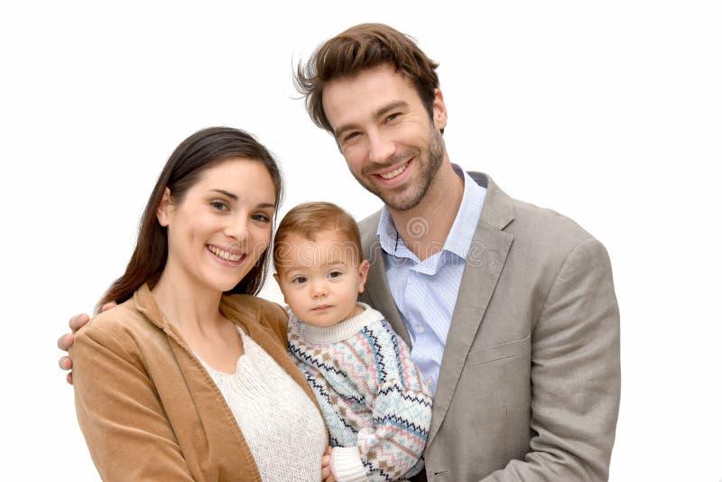 Ståenden av den lyckliga unga familjen med behandla som ett barn isolerat arkivbild