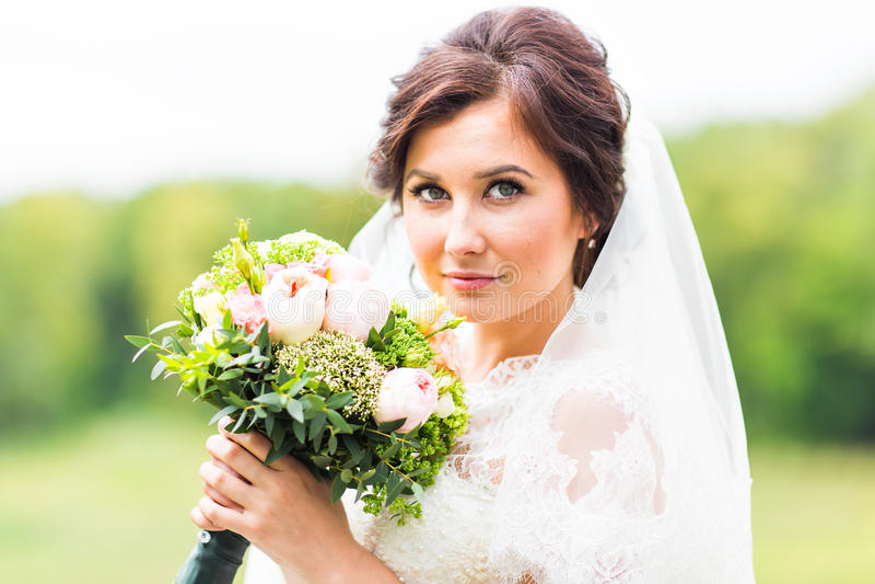 Ståenden av den lyckliga unga kvinnan i den vita bröllopsklänningen och brud- skyler med blommor royaltyfri bild