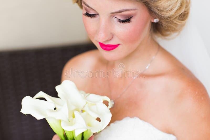 Ståenden av den lyckliga unga kvinnan i den vita bröllopsklänningen och brud- skyler med blommor royaltyfria foton