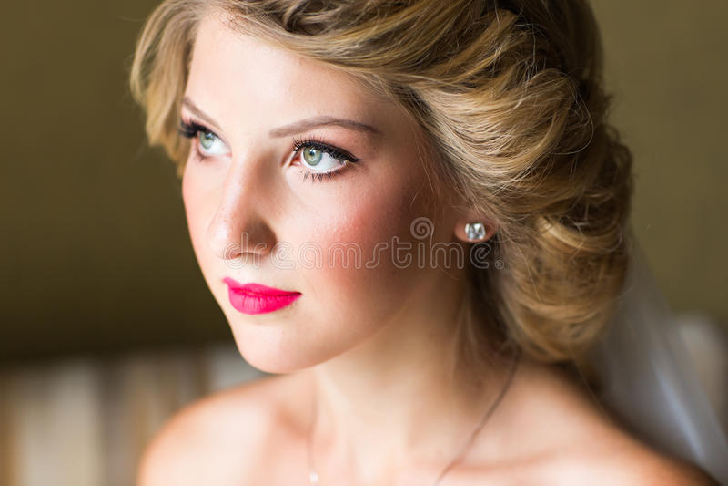 Ståenden av den lyckliga unga kvinnan i den vita bröllopsklänningen och brud- skyler med blommor fotografering för bildbyråer