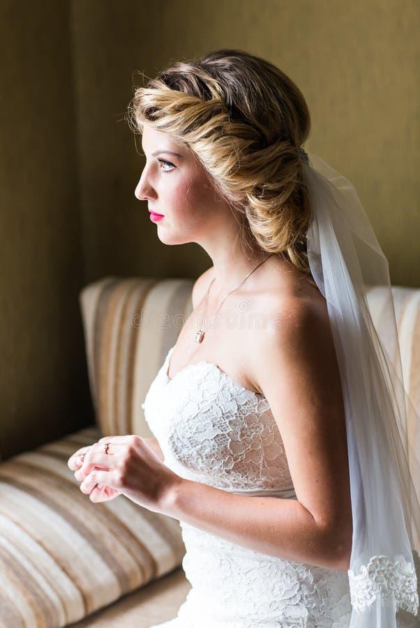 Ståenden av den lyckliga unga kvinnan i den vita bröllopsklänningen och brud- skyler med blommor arkivbilder