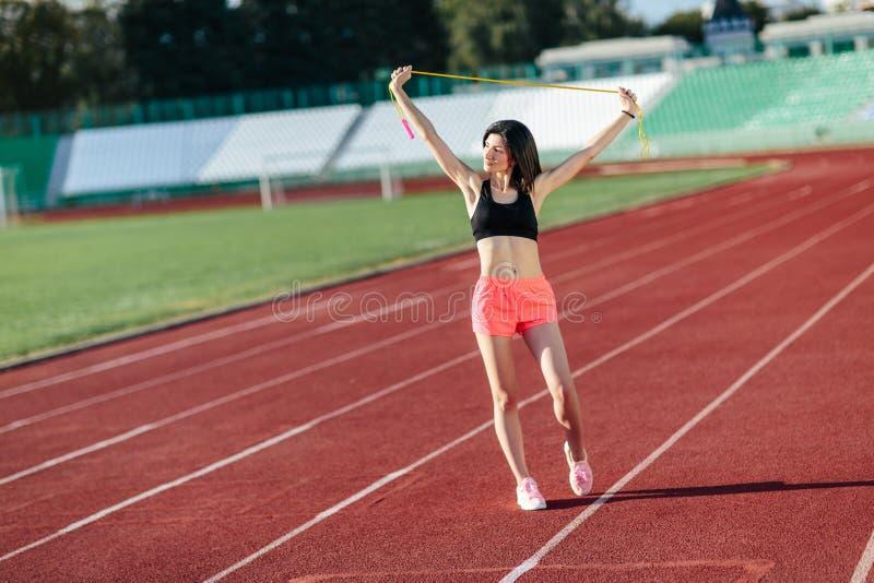 Ståenden av den lyckliga unga sportbrunettkvinnan i svart överkant och steg kortslutningar utomhus på stadion som rymmer överhopp royaltyfri fotografi