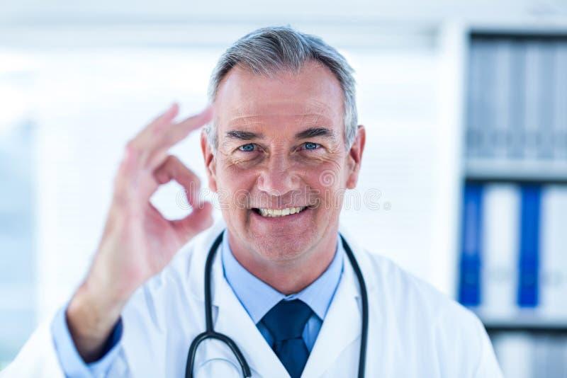 Ståenden av den manliga doktorn som ok visar, undertecknar in kliniken royaltyfri bild