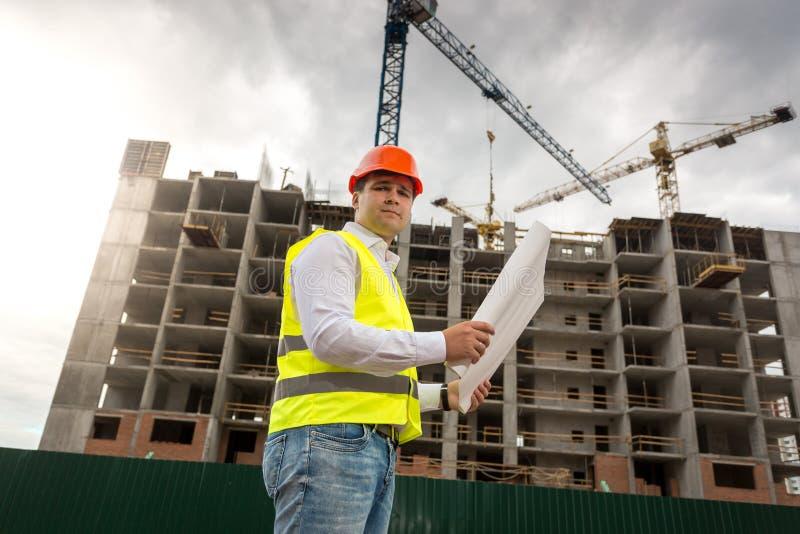Ståenden av den manliga teknikern i hardhat och säkerhet med ritningar som står mot funktionsduglig byggnad, sträcker på halsen arkivbild