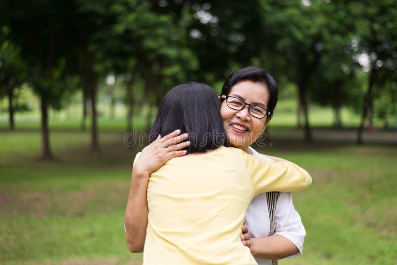 Ståenden av den mellersta åldriga asiatiska kvinnan med dottern som tillsammans står och kramar utomhus-, lyckligt och ler, reali royaltyfria foton