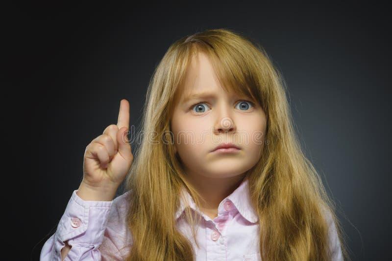 Ståenden av den missnöjda ilskna flickan med hotar fingret som isoleras på grå bakgrund closeup royaltyfri foto