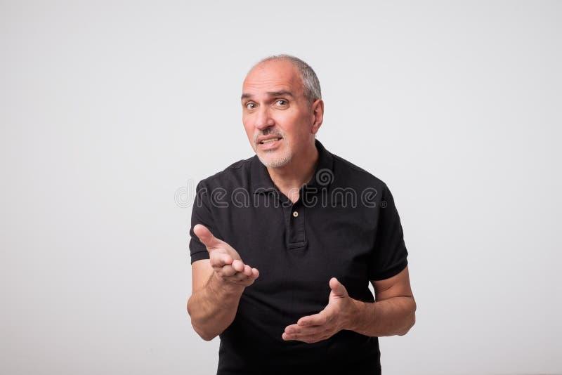 Ståenden av den mogna caucasianen en ung man som förvånas och frågas, ifrågasätter med den lyftta handen arkivfoton