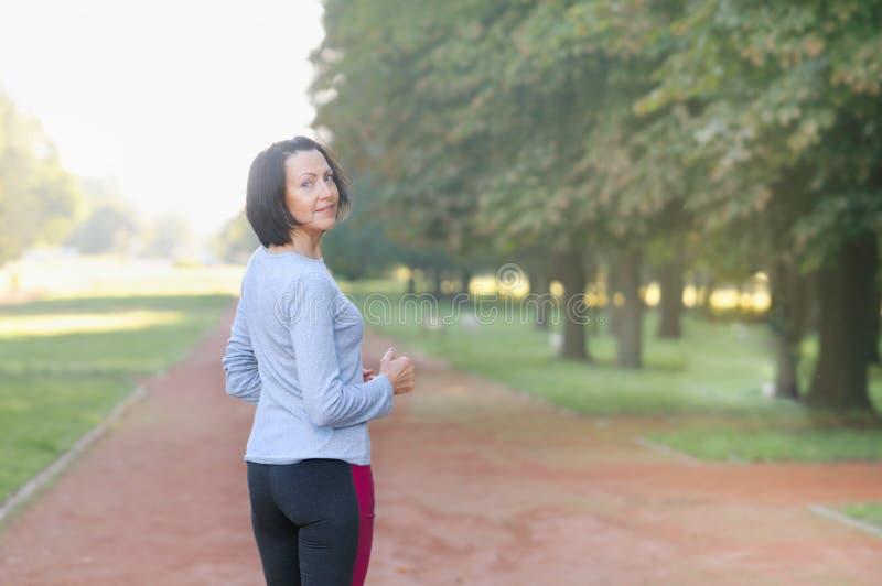 Ståenden av den mogna kvinnan för eller efter joggar i parkera royaltyfri fotografi