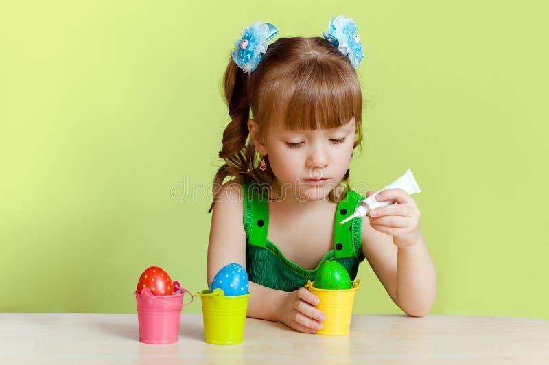 Den nätt liten flicka målar ägg royaltyfri bild