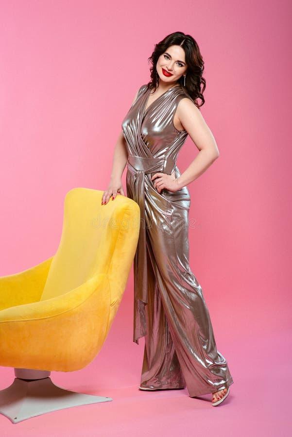 Ståenden av den nätta le attraktiva unga kvinnan för brunetten i silverdiskooveraller nära gulnar den stilfulla fåtöljen royaltyfri fotografi
