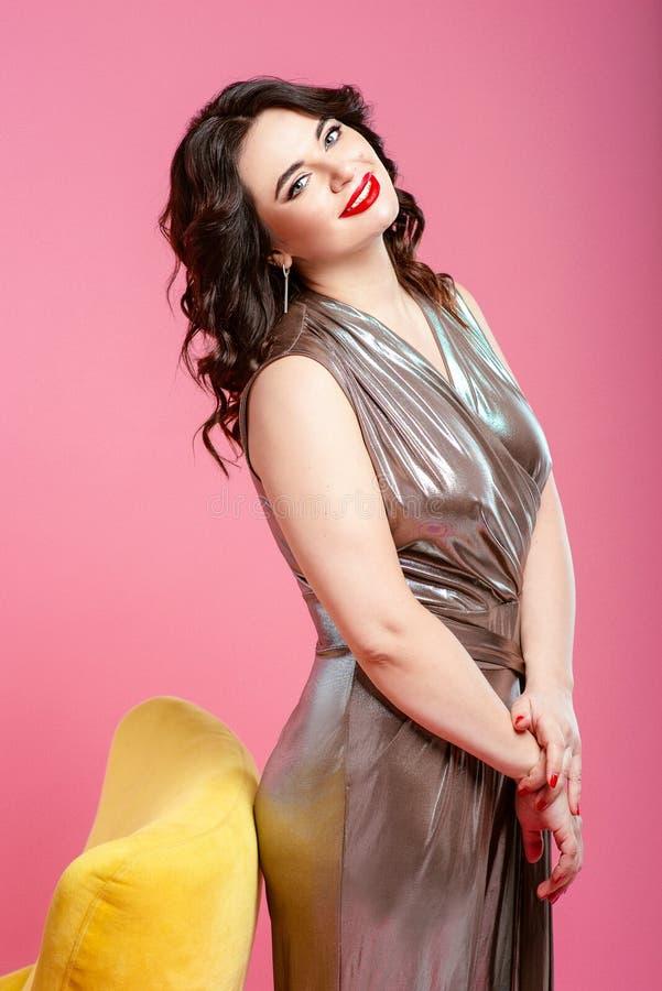 Ståenden av den nätta le attraktiva unga kvinnan för brunetten i silverdiskooveraller nära gulnar den stilfulla fåtöljen fotografering för bildbyråer