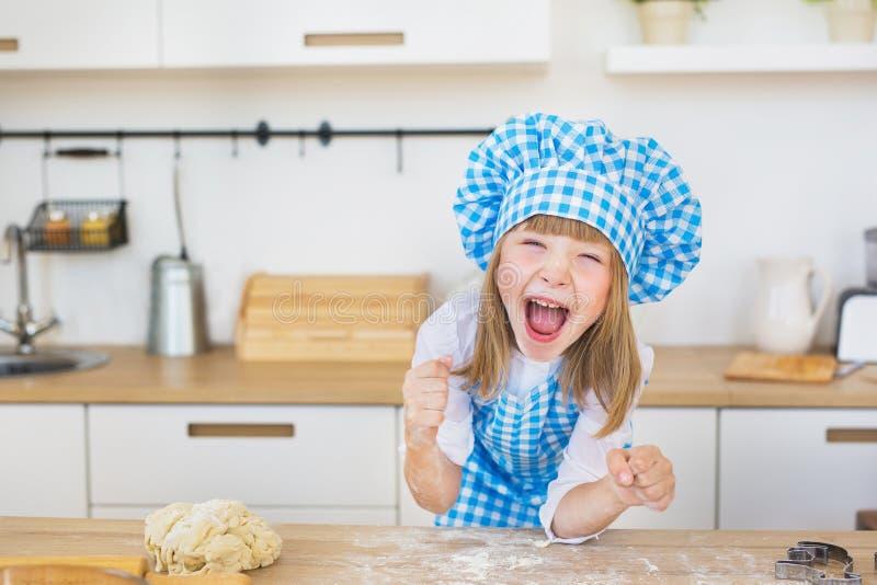 Ståenden av den nätta lilla flickan i en kock ser roliga skrin ett kök royaltyfria bilder