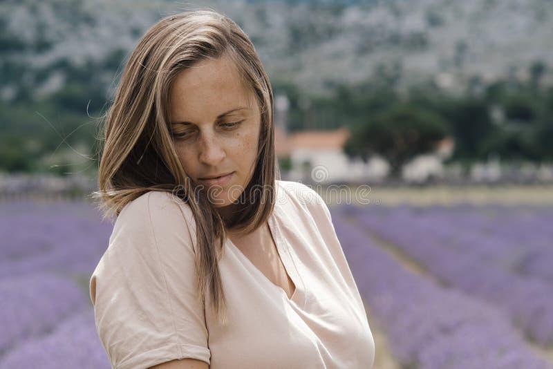 Ståenden av den nätta unga kvinnan med slut synar lukta blommor arkivfoto