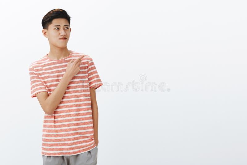 Ståenden av den nyfikna trevliga unga asiatiska manliga modellen i randigt t-skjorta anseende kopplade av över den gråa väggen me arkivfoto